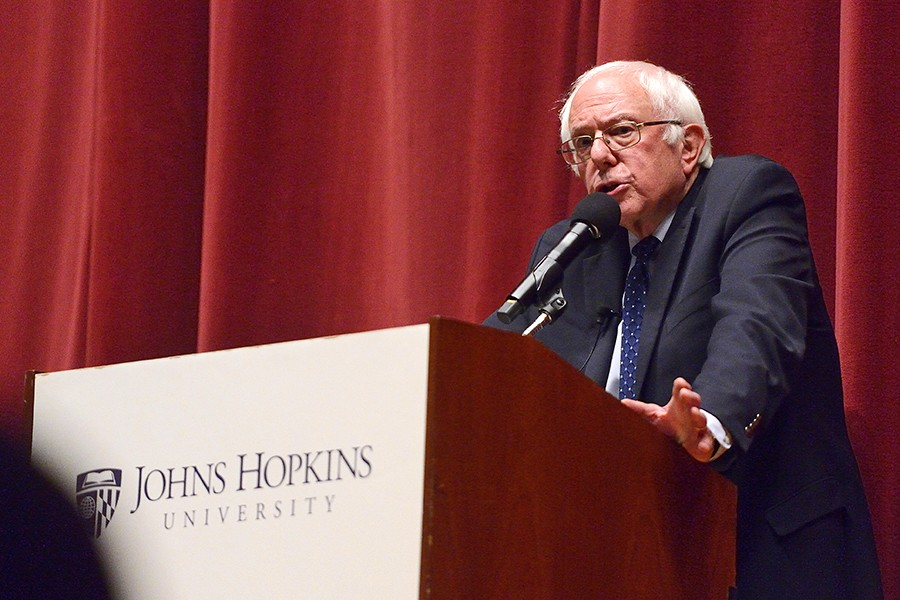 Sen. Bernie Sanders at podium with red curtain backdrop