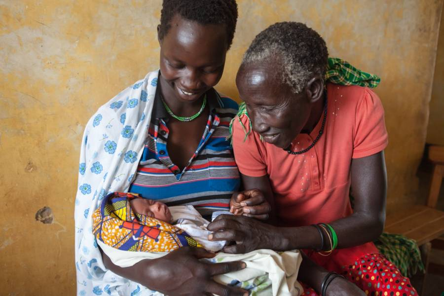 Two women look at a newborn baby