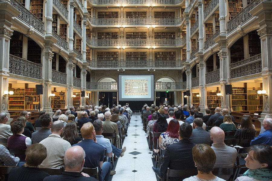 A center aisle divides seats at a presentation inside the historic George Peabody Library