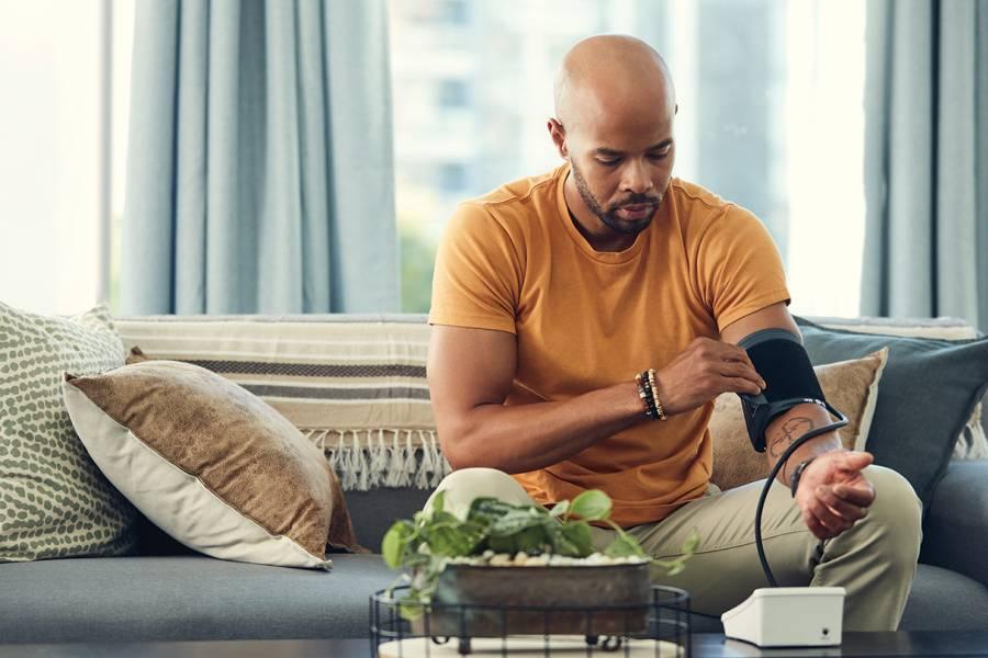 A Black man takes his blood pressure