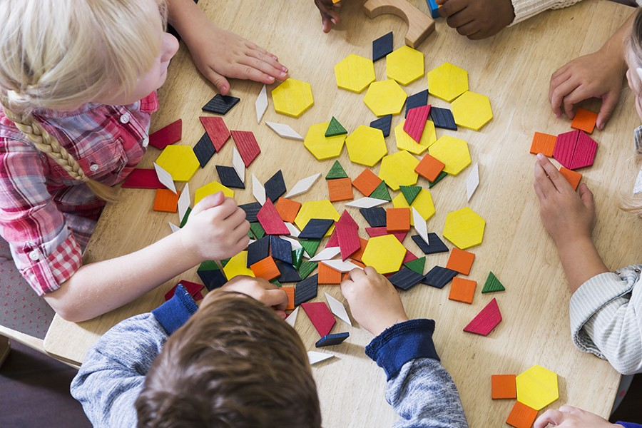 Four young kids sit at a table and play with colorful blocks in various shapes including square, hexagon, rhombus, and trapezoid