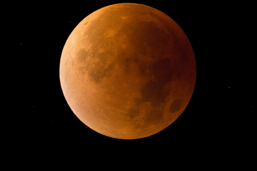 The moon appears in a reddish orange glow