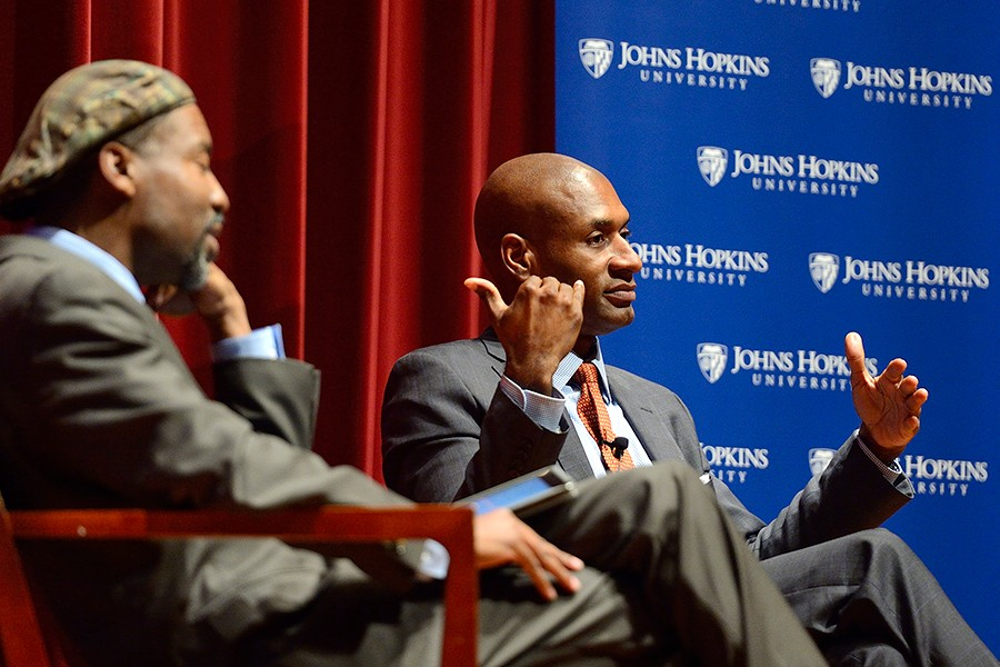 Charles Blow (right) responds to a question while seated on stage in front of a blue Johns Hopkins banner; moderator Lester Spence is seated to Blow's right
