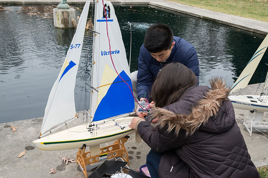 Two students prepare sailboat to race in fountain