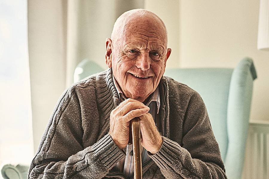 Smiling elderly man sitting at home leaning on cane
