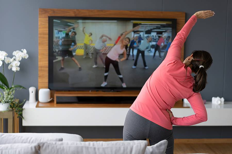 Woman exercising at home along with a class on her smart TV screen