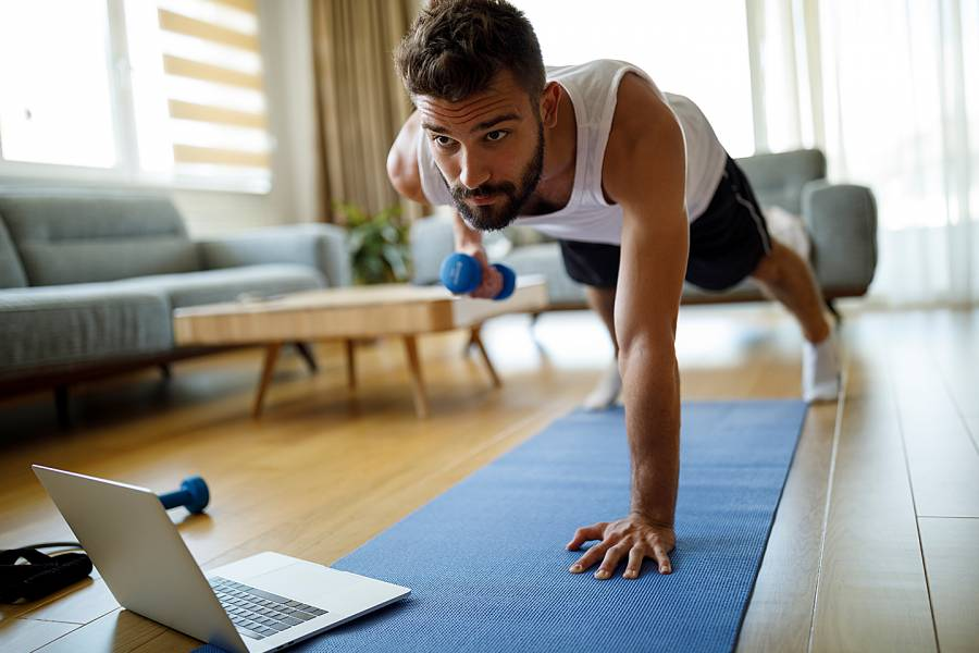 Man exercizing in his living room while looking at his laptop screen