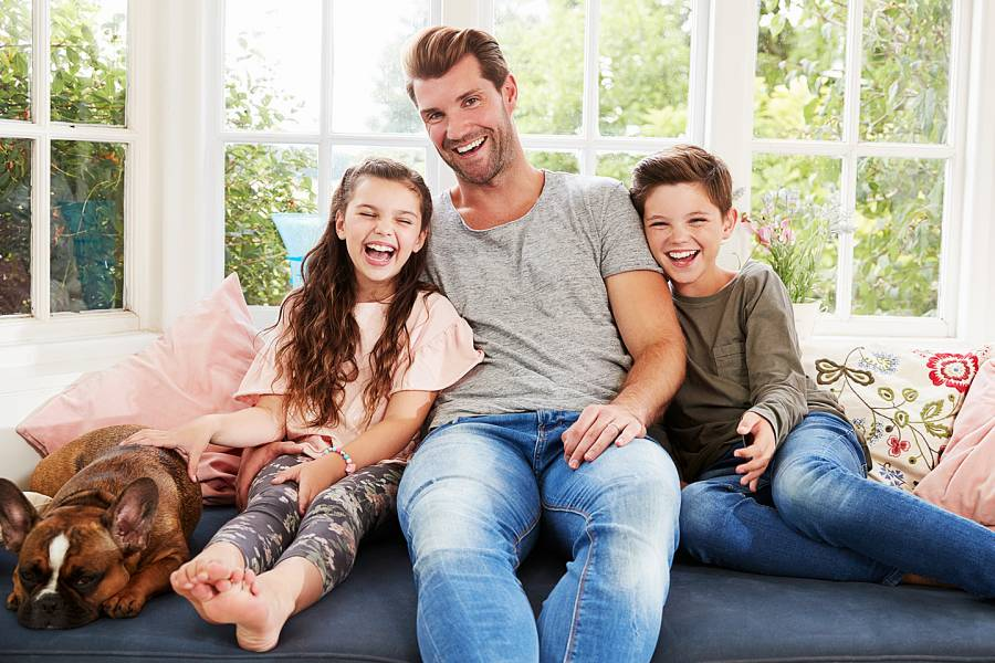 Smiling father and two kids sitting on a couch