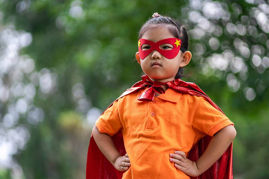 Young girl playing in superhero costume