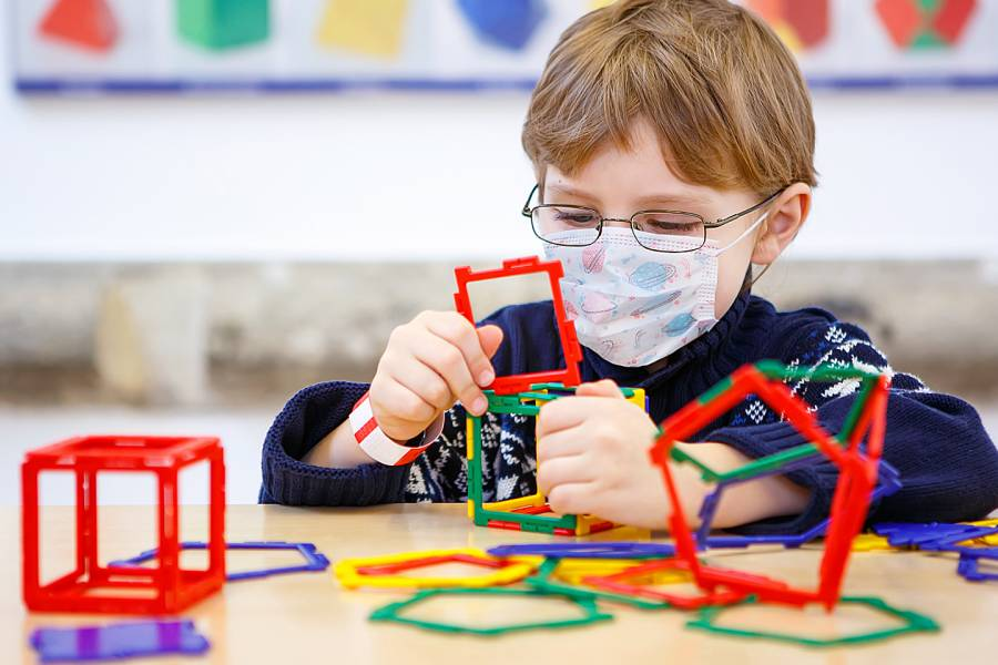 Young boy playing with toys at child care facility