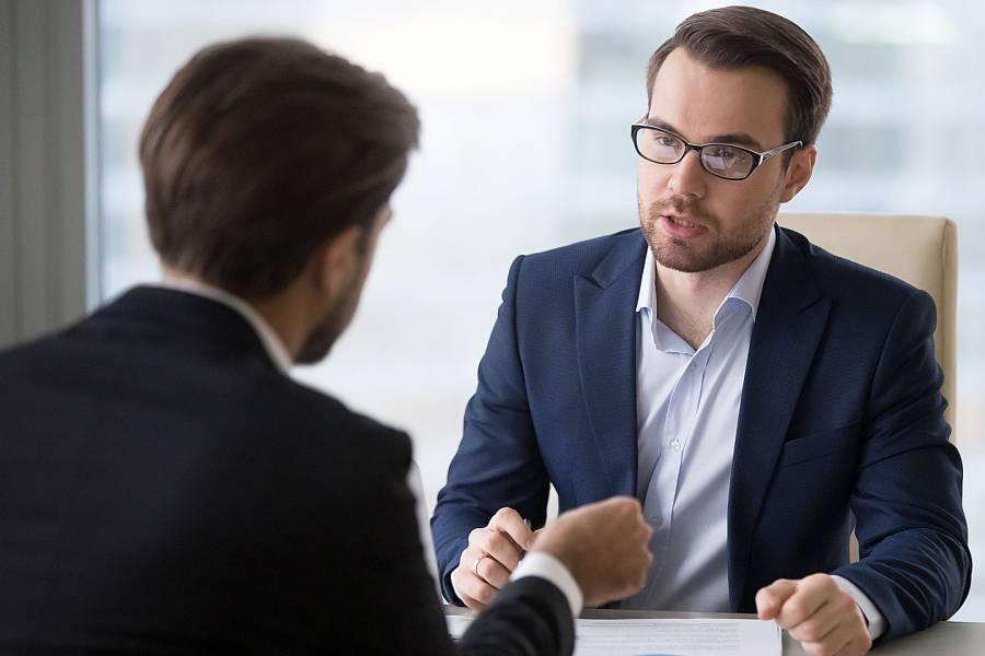 Two men having a civil conversation across a desk