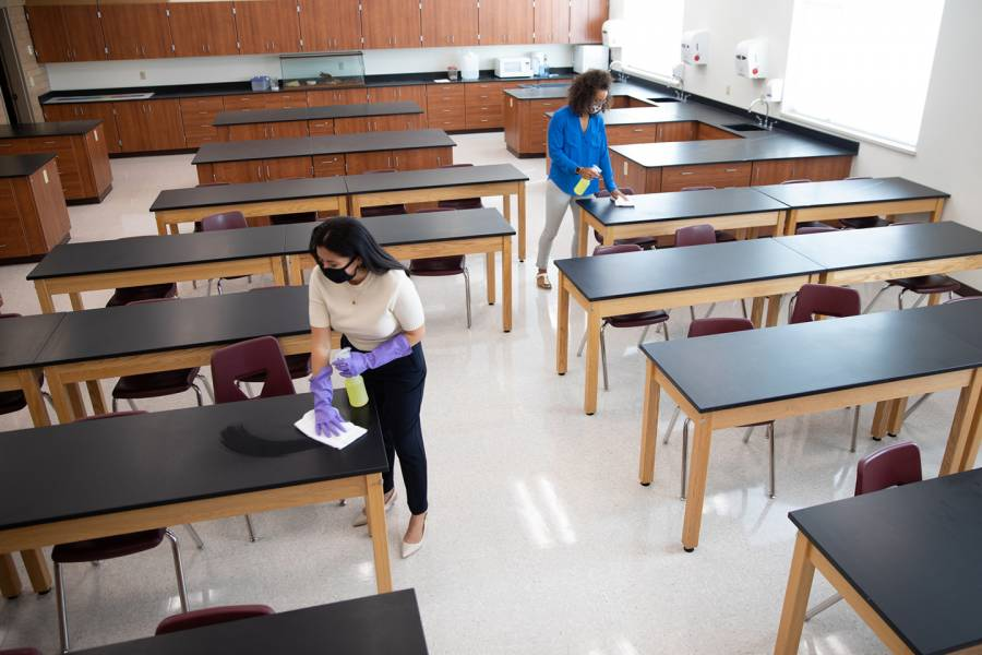 Two instructors clean a laboratory classroom