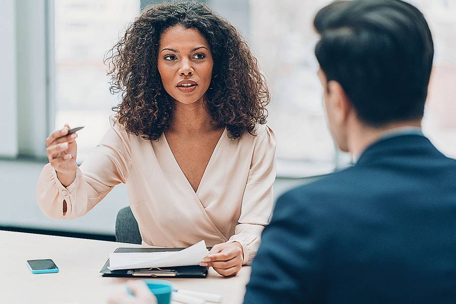 Woman sitting at desk talking with male colleague