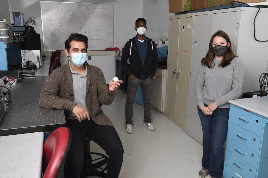 Team of three people in masks holding a small round device in a lab space