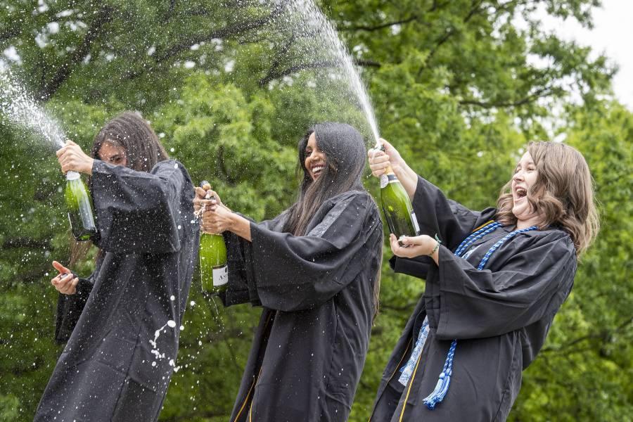 Women in Commencement regalia spray champagne