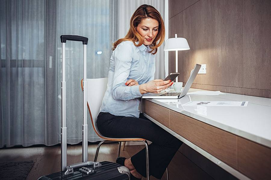 Woman in hotel room working with her laptop and mobile phone