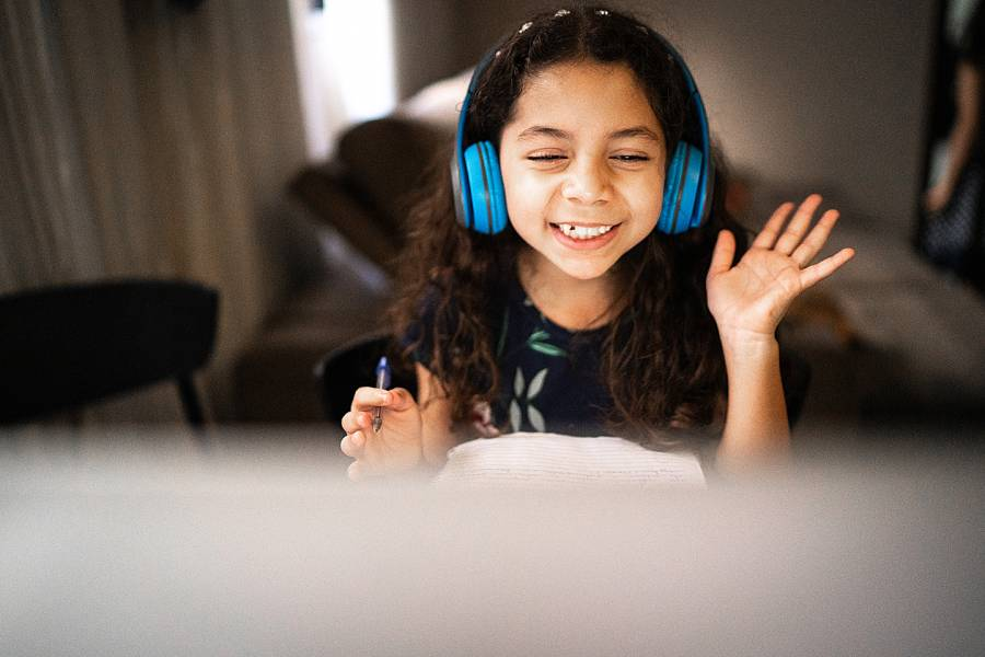 Young girl at computer wearing headphones