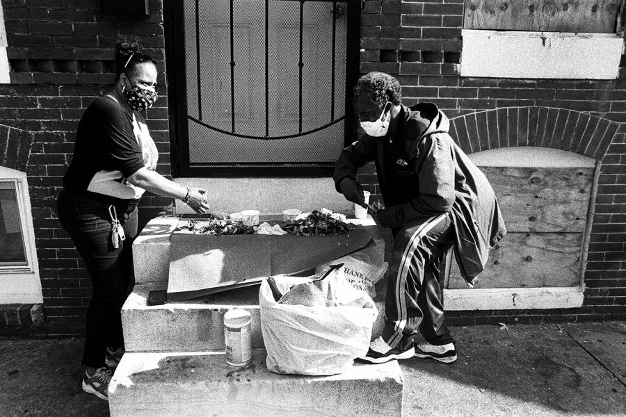 Two people eat crabs on a stoop in Baltimore