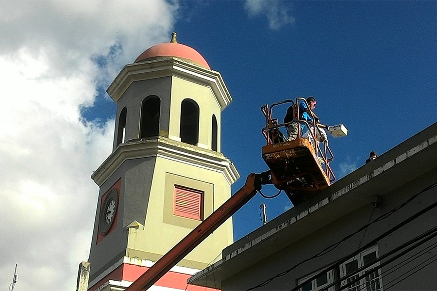 Crane elevates man to a rooftop position with church steeple in background