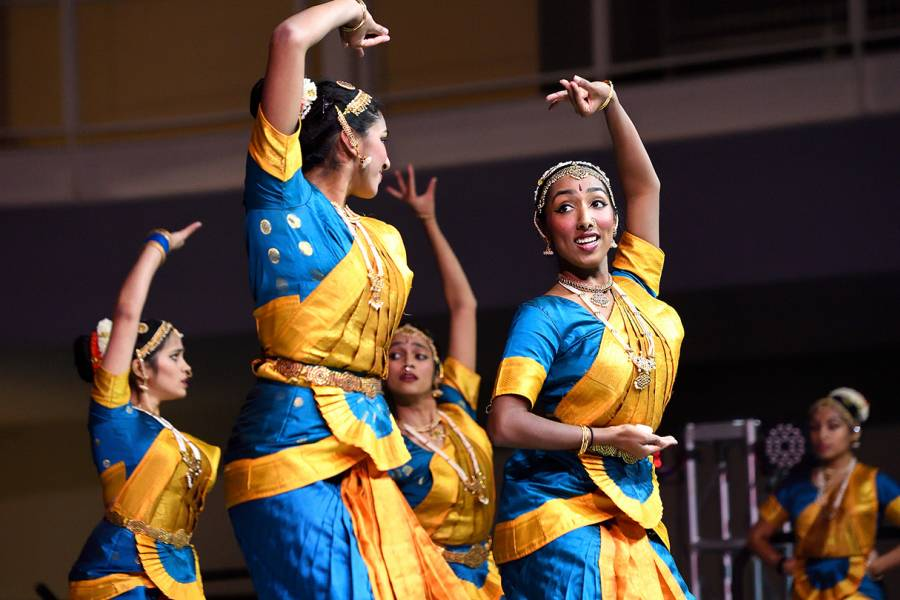 Students in saris perform a synchronized dance