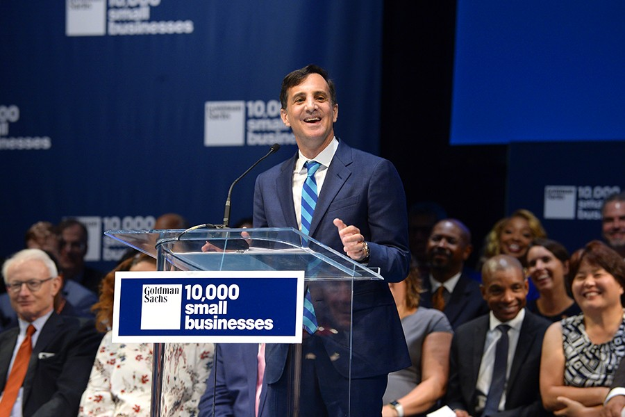 President Ronald J. Daniels at podium adorned by 10,000 Small Businesses sign