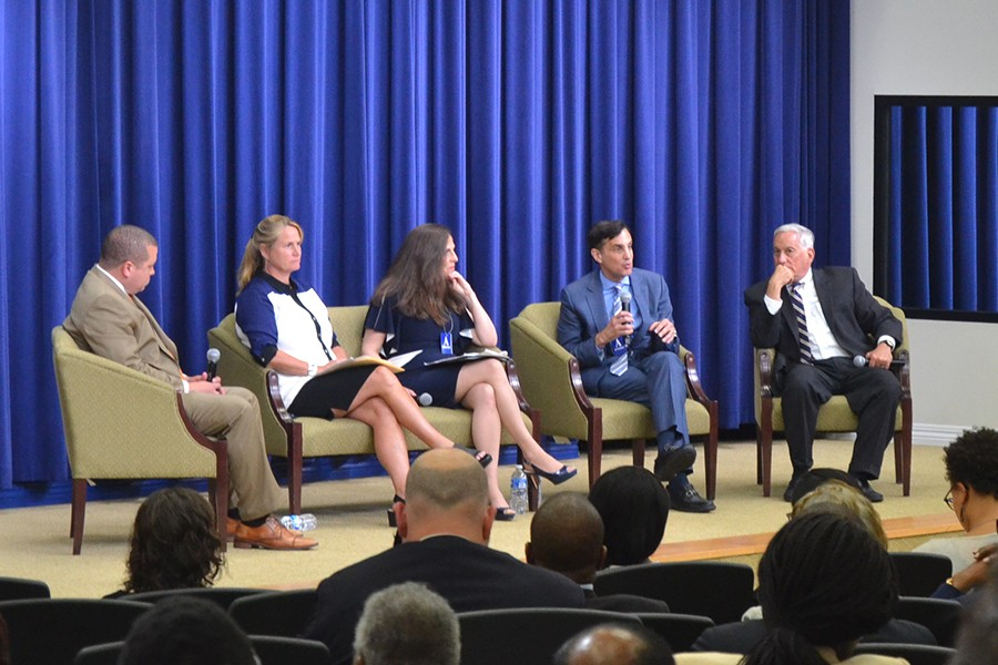 Five panelists in front of a blue curtain
