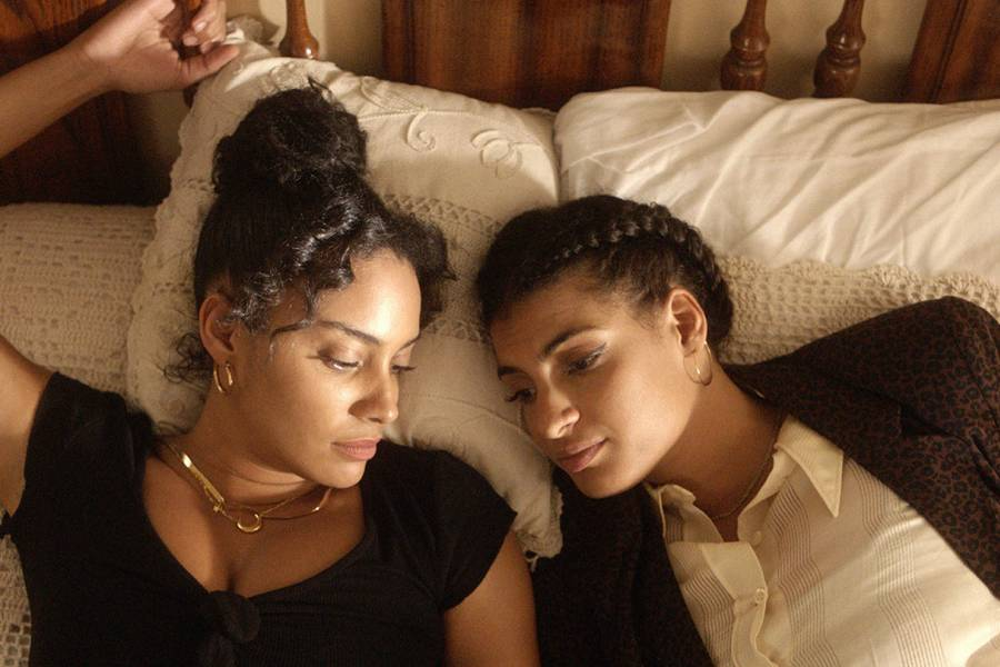 In this scene from De Lo Mio, two sisters lay on their grandfather's bed