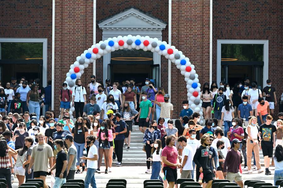 Students walk out of Shriver Hall under red, white, and blue balloon arch on Democracy Day