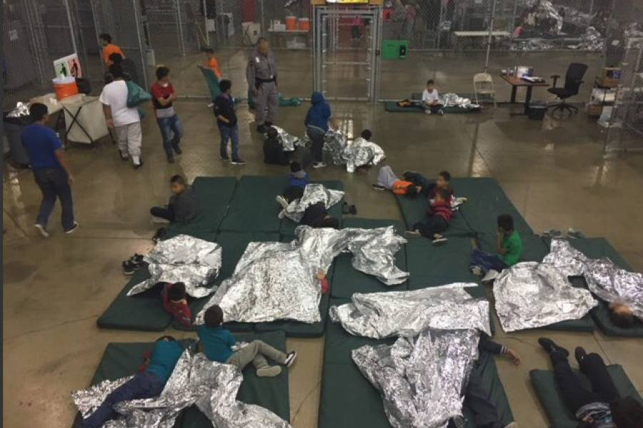 Children sit on mats with shiny silver blankets at a detention facility