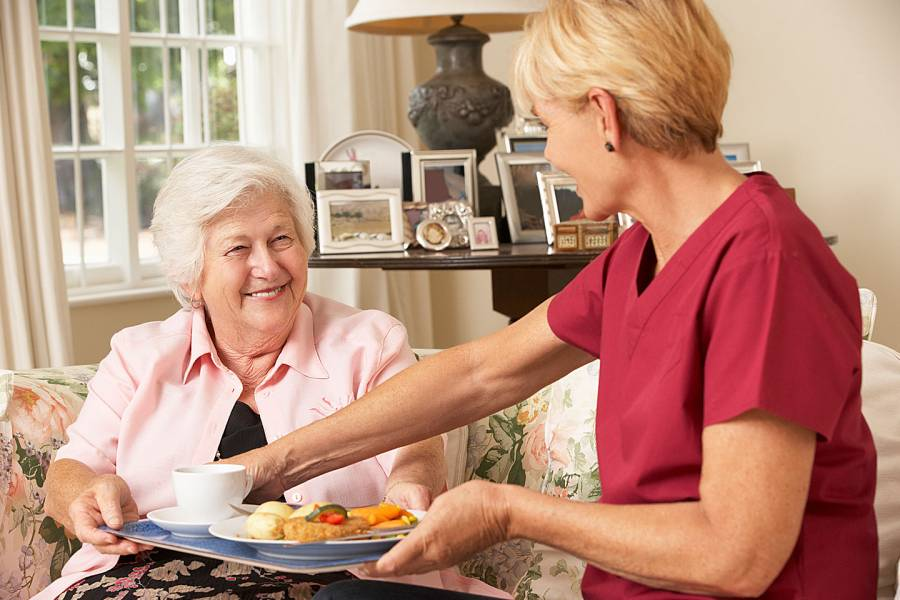 Helper serving senior woman with meal in care home