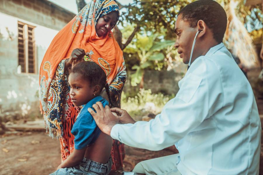 A doctor examines a child in Africa