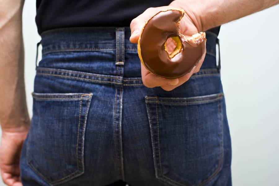 Man holding chocolate donut behind his back