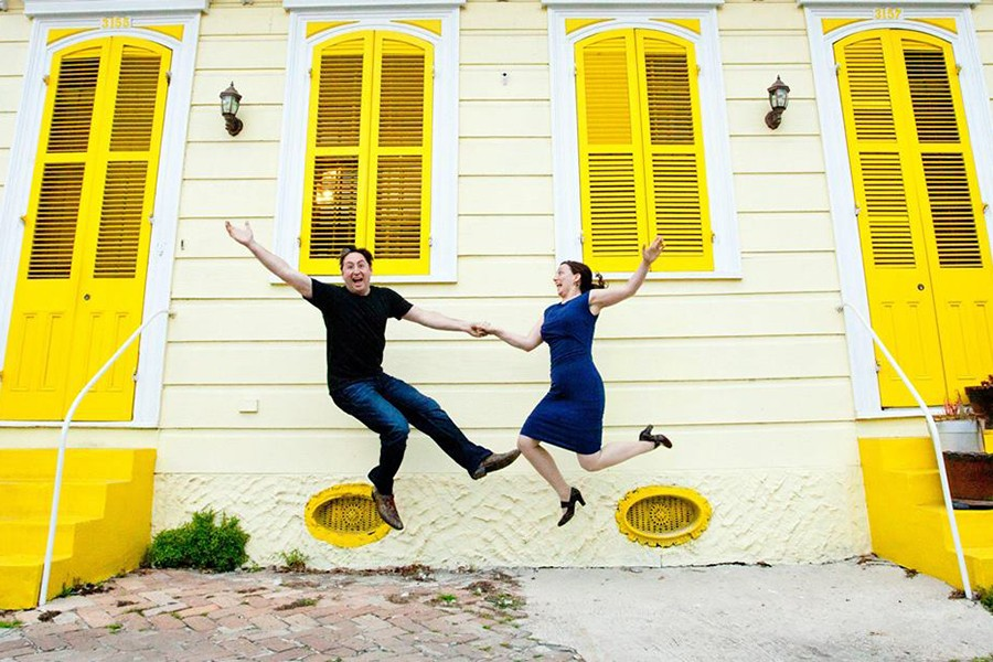 A man and woman hold hands and leap in the air in front of bright yellow row homes