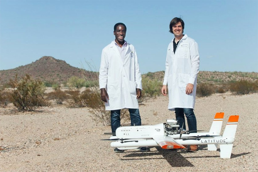 Two men in white lab coats pose next to drone in a desert setting