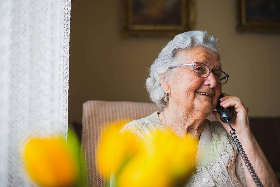 Elderly woman smiling while talking on the phone