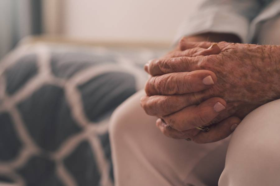An elderly person sits with their hands clasped together