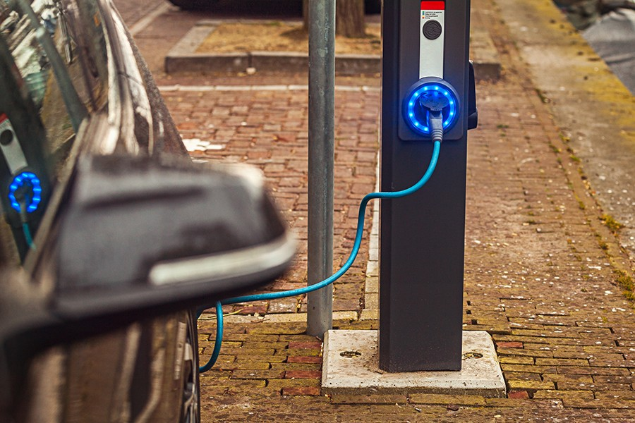 An electric car is plugged into a charging station which is lit with blue LED lights