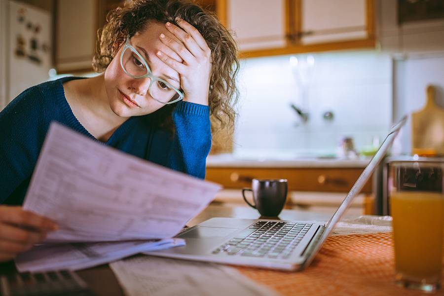 Woman appearing upset when looking at financial information