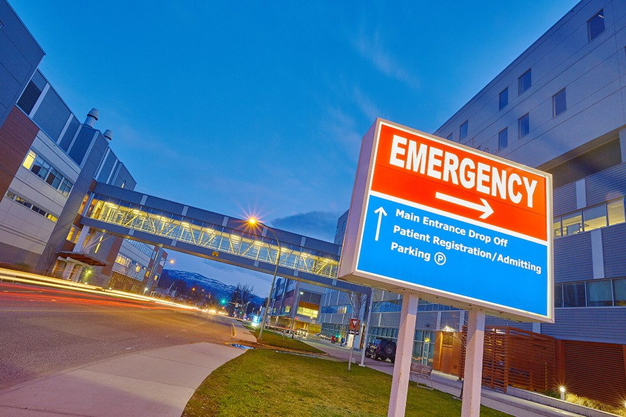 Red emergency sign with arrow pointing right outside of hospital