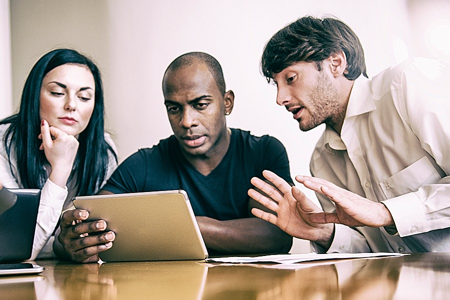 Photo shows a woman and two men looking at the screen of a laptop.
