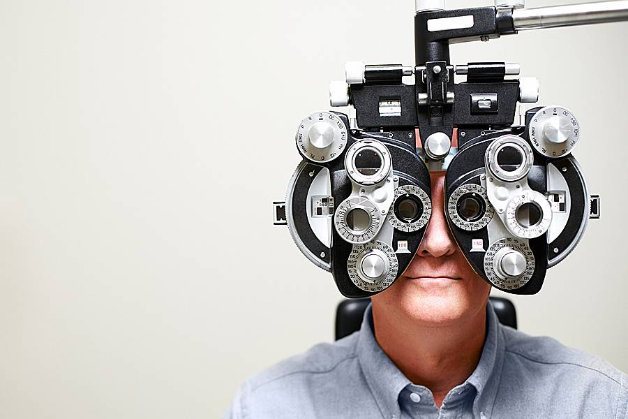 Man looking through an ophthalmic instrument called a phoroptor
