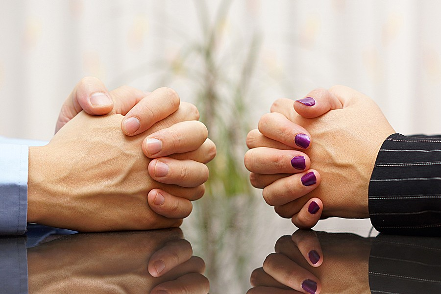 Closeup of two pairs of clenched hands facing each other across a table