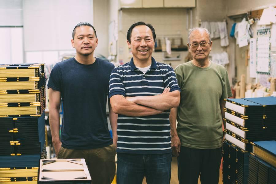 Three generations of craftsmen stand in their workshop