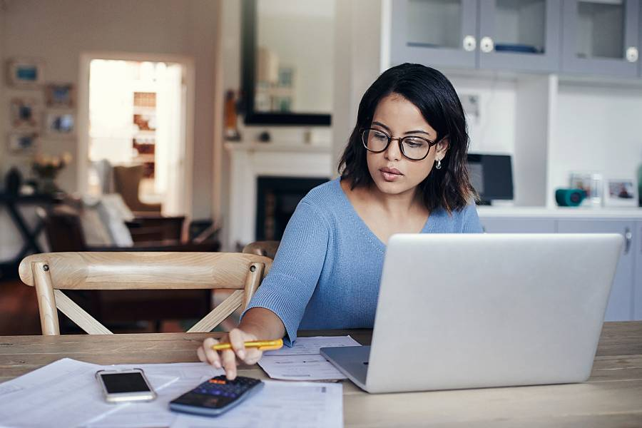 Woman working on her budget at her dining table
