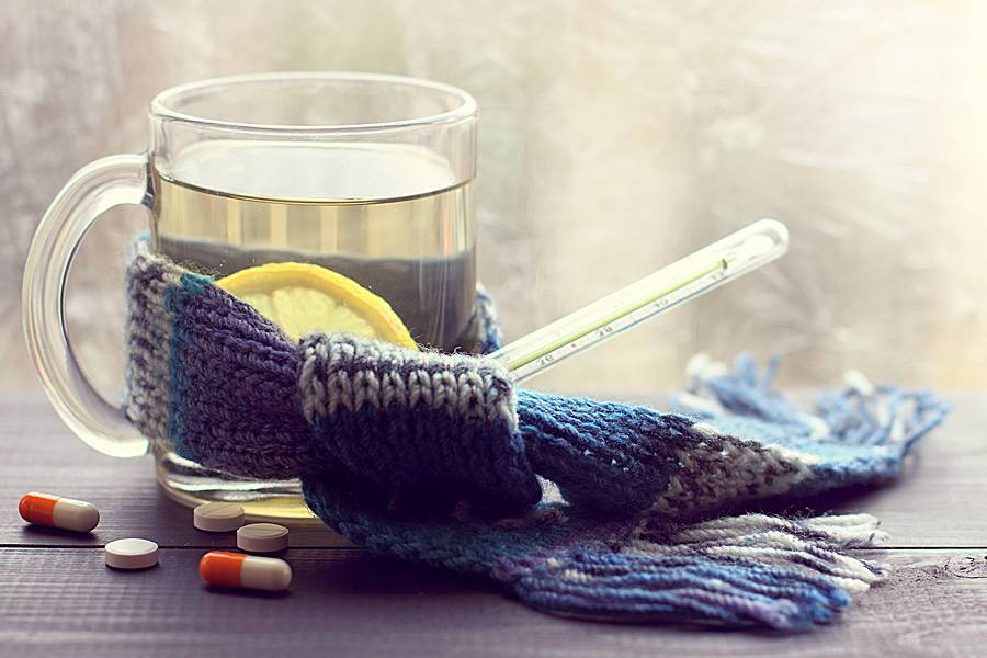 Lemon-infused hot drink in a transparent mug wrapped with a scarf and thermometer, medicine on the table