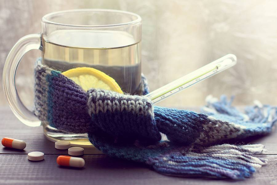 Mug of hot water with lemon and a thermometer wrapped in a knitted scarf