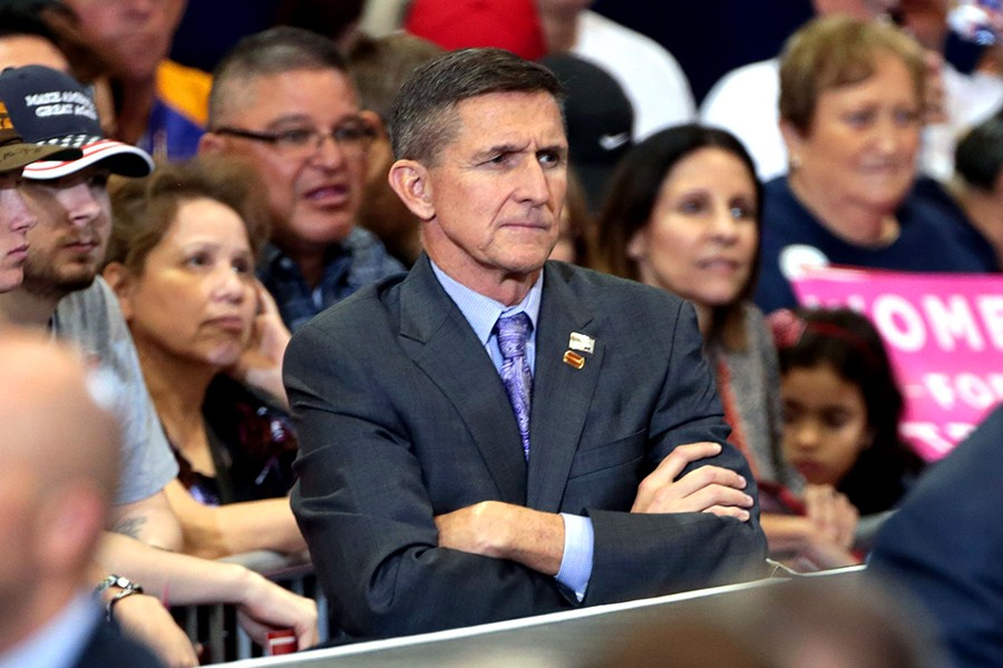Michael Flynn stands with arms crossed in front of Trump supporters at rally