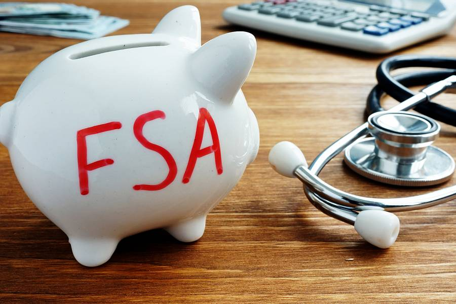 Piggybank with FSA written on it, next to a stethoscope