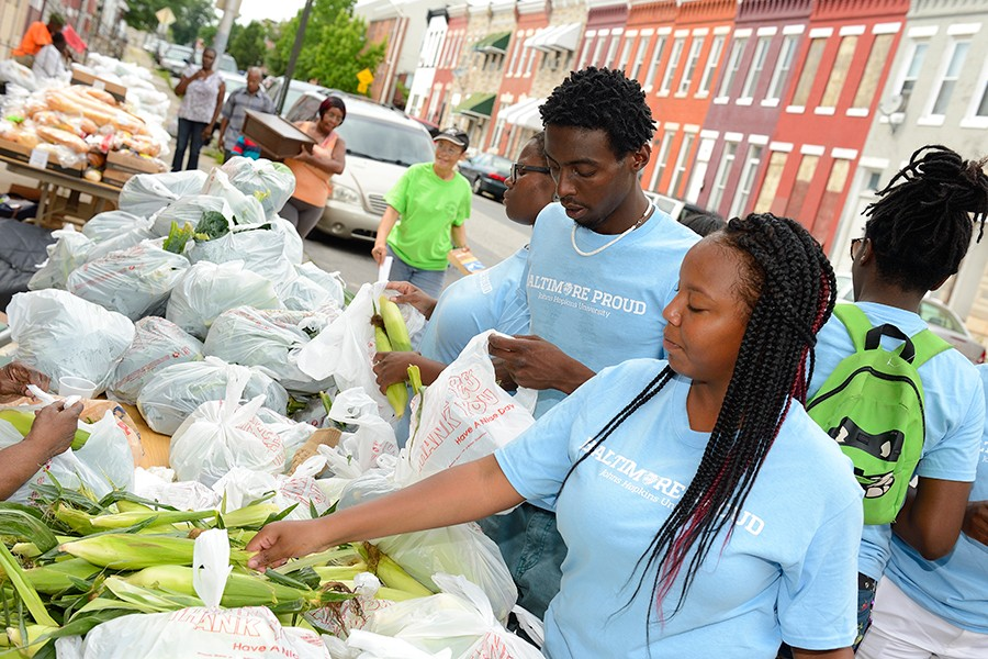 Volunteers sort fresh corn at food outreach event