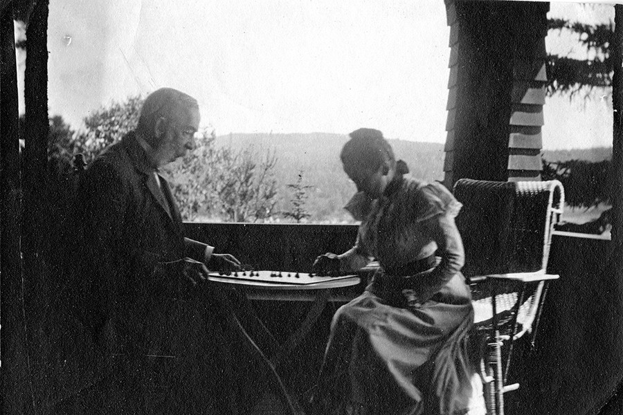 In a grainy black and white photo, two people play chess